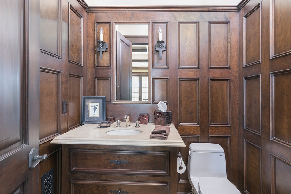 This powder roo has consistent dark wooden tones to its walls and vanity cabinet that contrasts the white porcelain toilet. Image courtesy of Toptenrealestatedeals.com.