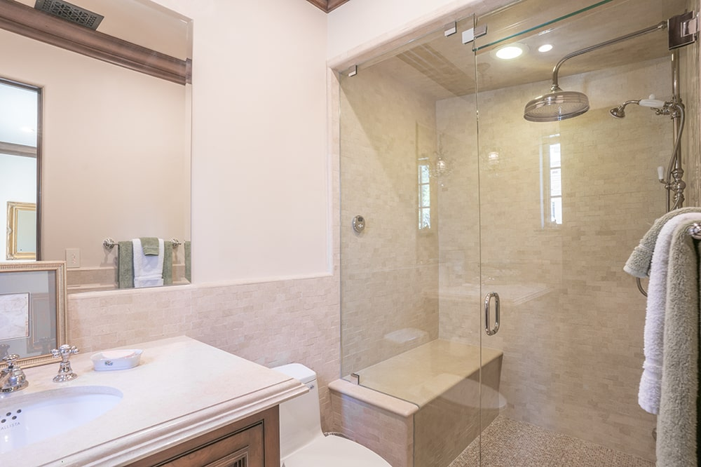 The bathroom walk-in shower area has a built-in bench fitted with the same tiles as the walls. Image courtesy of Toptenrealestatedeals.com.