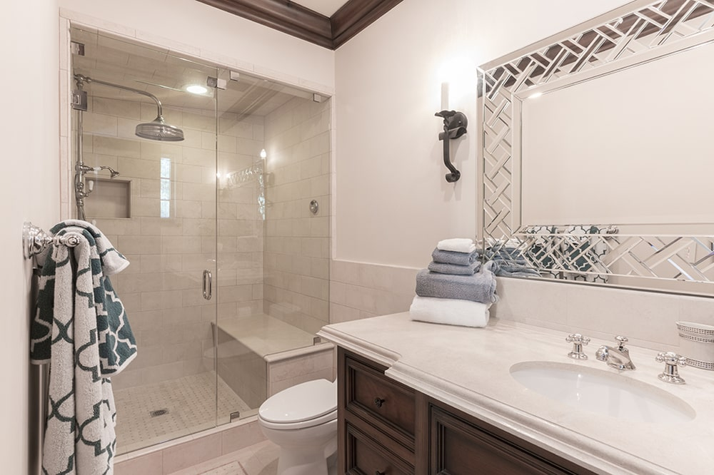 The dark wooden vanity is topped with an intricate wall-mounted mirror with sconces on the side. Image courtesy of Toptenrealestatedeals.com.