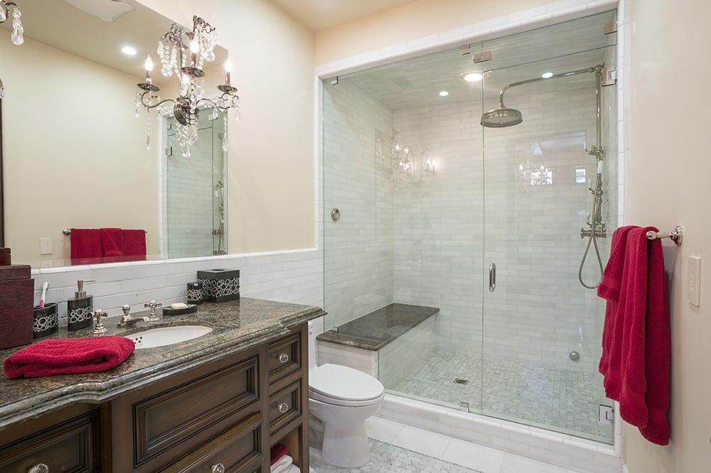 This farther look of the bathroom shows the dash of vibrant red tones on the beige walls. Image courtesy of Toptenrealestatedeals.com.