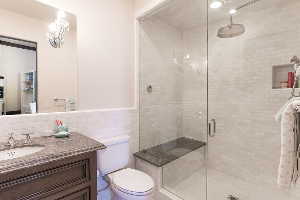 The glass-enclosed shower are of the bathroom has a dark bench that stands out against the beige tiles. Image courtesy of Toptenrealestatedeals.com.
