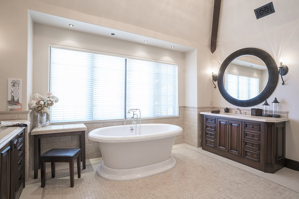 This bathroom has a freestanding bathtub by the window that brings in an abundance of natural lighting to complement the beige tones.Image courtesy of Toptenrealestatedeals.com.