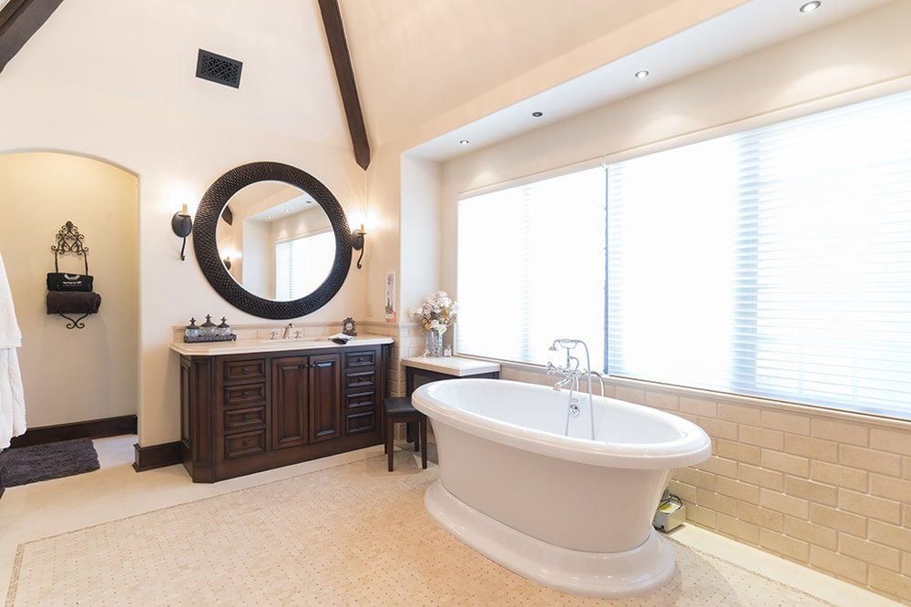 The dark wooden vanity on the far side has a matching round mirror. These stand out against the beige walls and the white bathtub on the side. Image courtesy of Toptenrealestatedeals.com.