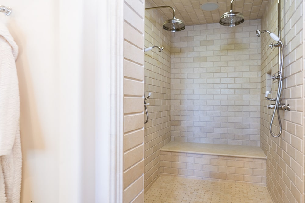 This is a closer look at the walk-in shower area with beige tiles on its floor and walls. Image courtesy of Toptenrealestatedeals.com.