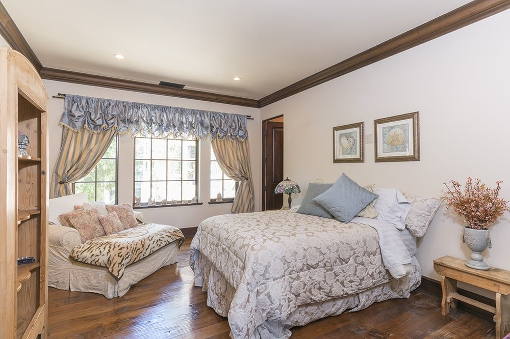 The patterned sheets of the bed matches well with the couch on the side of the row of windows that has curtains. Image courtesy of Toptenrealestatedeals.com.