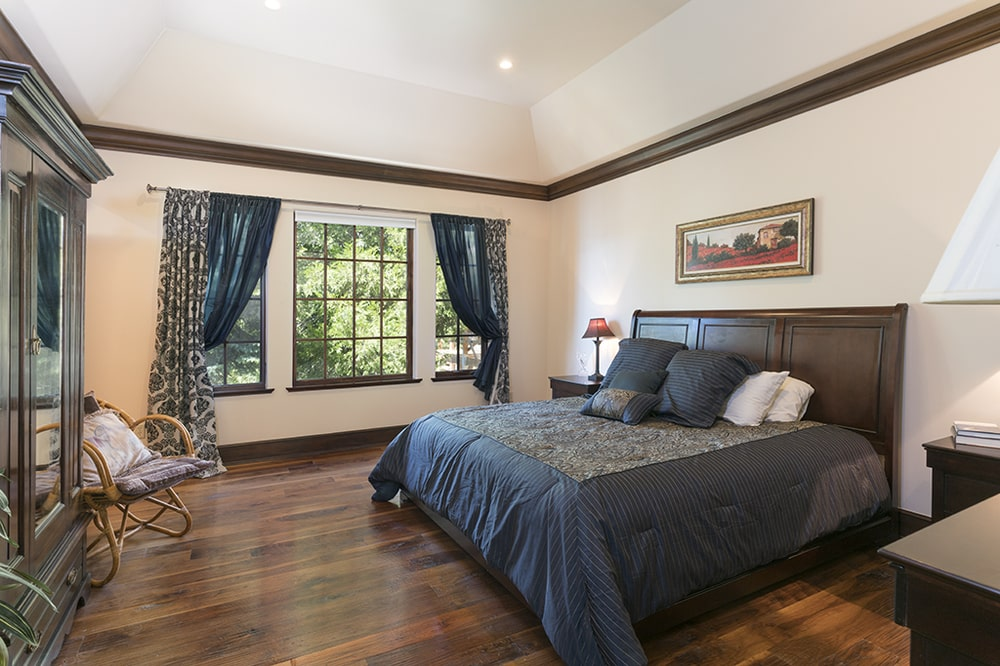 The wooden headboard of the bed stands out against the beige walls of this bedroom that is adorned with a wall-mounted painting. Image courtesy of Toptenrealestatedeals.com.
