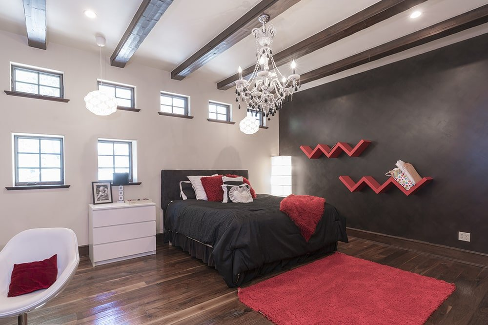 This bedroom has a black wall adorned with red floating shelves. This matches with the tone of the bed and the area rug at its foot. Image courtesy of Toptenrealestatedeals.com.