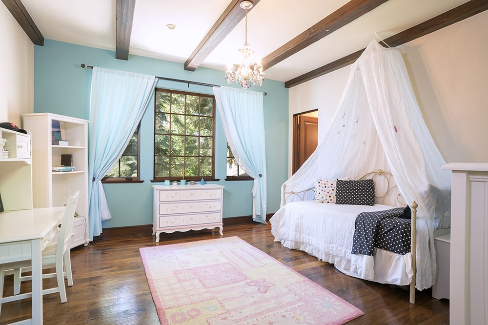 This is the kids bedroom with a pastel-toned wall on the far side. Across from the bed is a work and study area. Image courtesy of Toptenrealestatedeals.com.