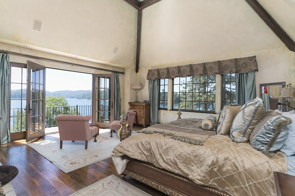 The bed of this bedroom has a view across from it by the sitting area. It has a set of folding doors that open to the balcony. Image courtesy of Toptenrealestatedeals.com.