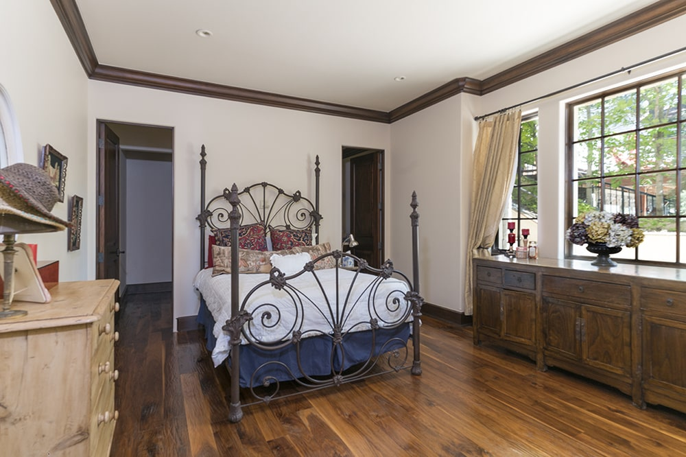 This bedroom has an intricate wrought-iron bed. On the side of this is a dark dresser that blends well with the dark hardwood flooring. Image courtesy of Toptenrealestatedeals.com.