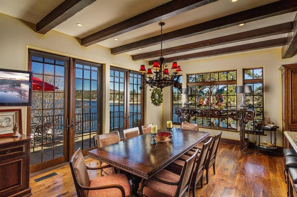 The formal dining room has a large rectangular dining table topped iwth a decorative chandelier hanging from a ceiling that has exposed wooden beams. Image courtesy of Toptenrealestatedeals.com.