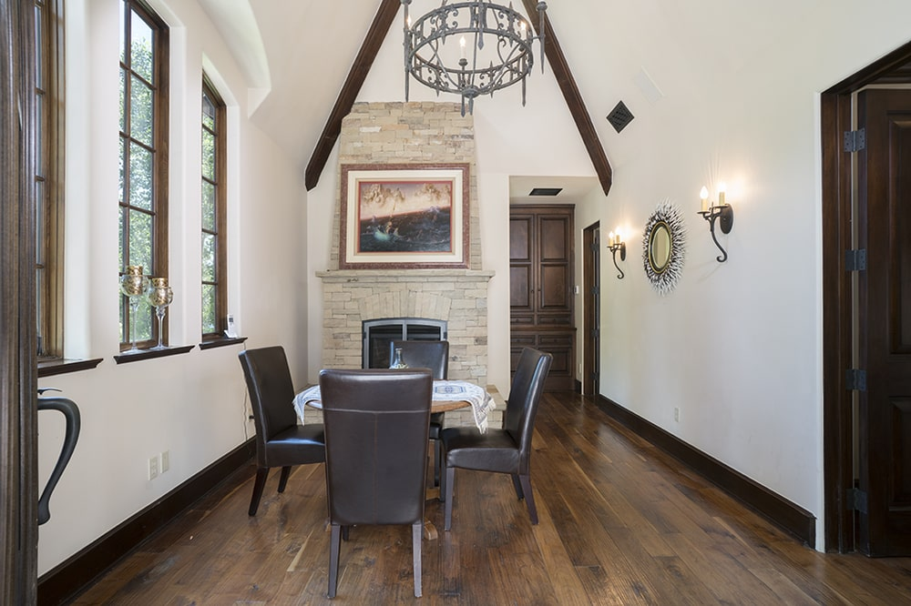 This informal dining area has a tall arched ceiling with a round wrought-iron chandelier hanging over the dining table that matches well with the chairs. Image courtesy of Toptenrealestatedeals.com.