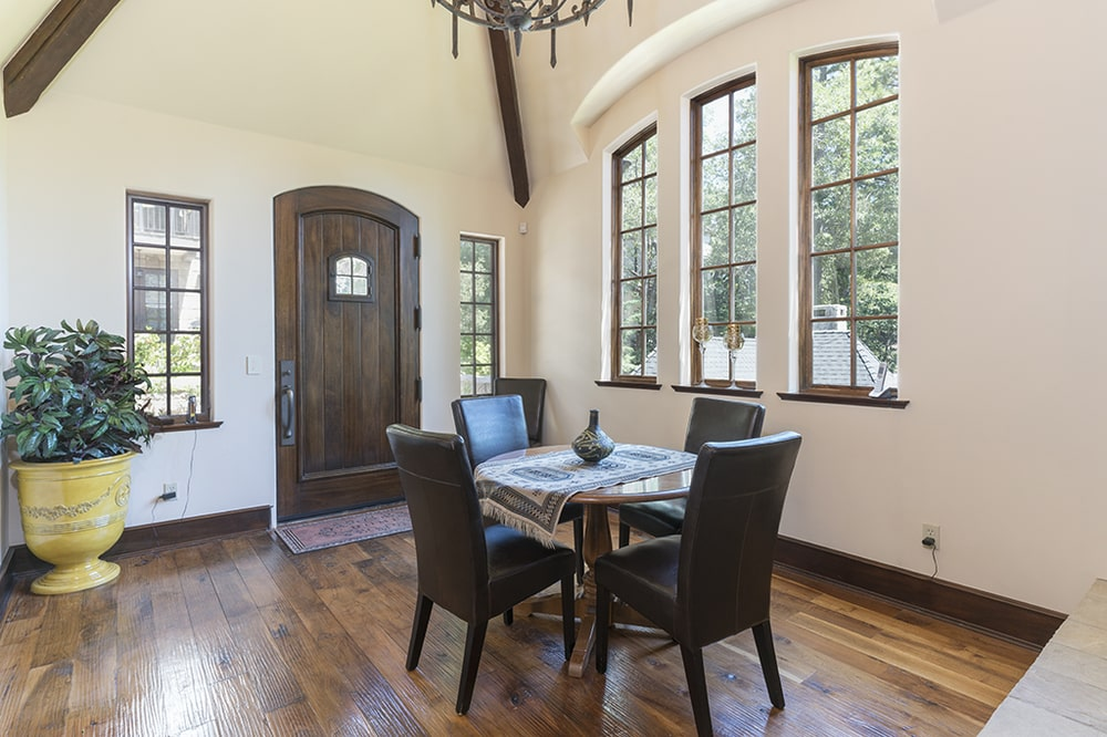 This other look at the informal dining area gives a look at the rows of tall windows that bring in natural lighting to brighten the dark hardwood flooring. Image courtesy of Toptenrealestatedeals.com.
