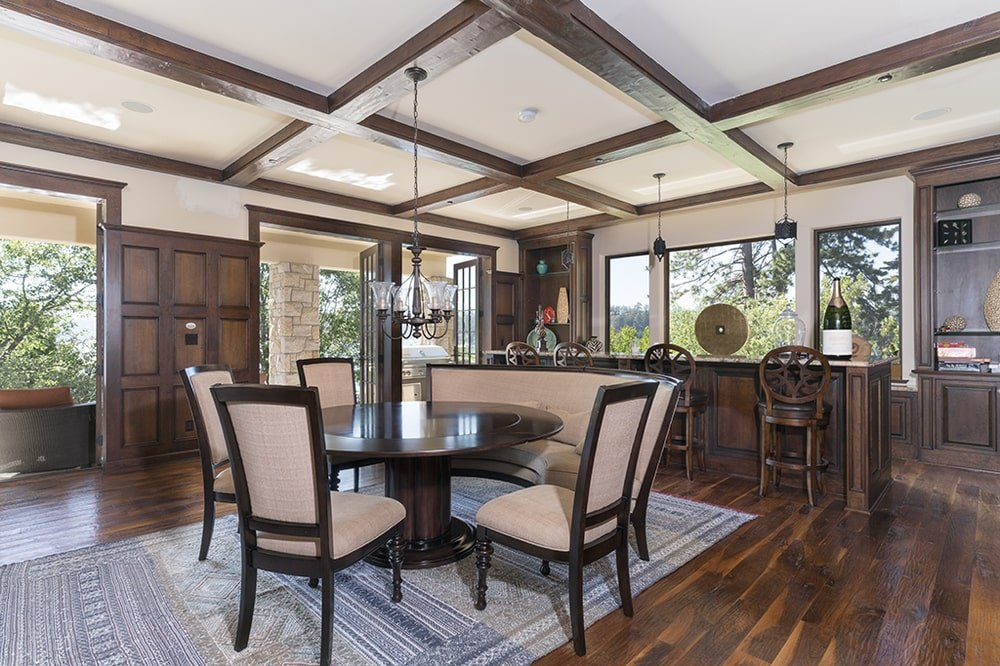 This other view of the dining room shows that the ceiling hangs a small chandelier over the table and that there is also a curved cushioned bench beside the table. Image courtesy of Toptenrealestatedeals.com.