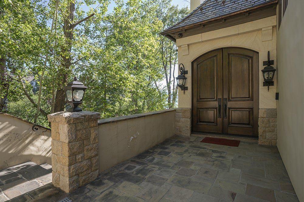 This is a closer look at the main entrance of the house with a pair of dark wooden arched doors complemented by the beige exterior walls. Image courtesy of Toptenrealestatedeals.com.