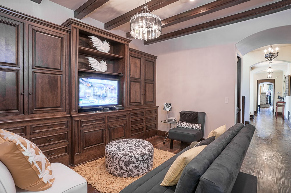 The cozy family room has a dark gray sofa that stands out against the beige area rug paired with a cushioned ottoman for a coffee table. Image courtesy of Toptenrealestatedeals.com.
