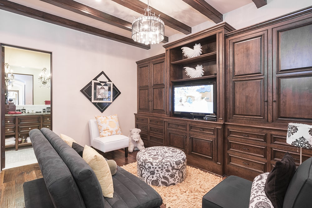 This other view of the family room shows more of the dark wooden structure across from the sofa that has built-in cabinets, shelves and TV. Image courtesy of Toptenrealestatedeals.com.