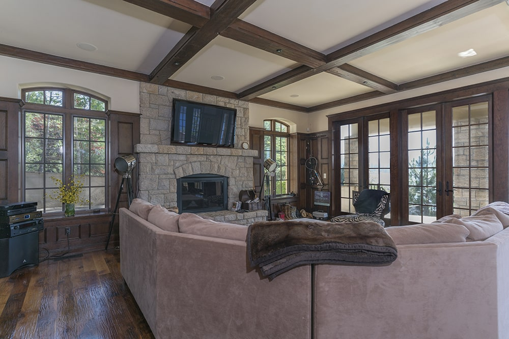 This other family room has a large curved sectional sofa that faces a stone fireplace topped with with a wall-mounted TV. Image courtesy of Toptenrealestatedeals.com.
