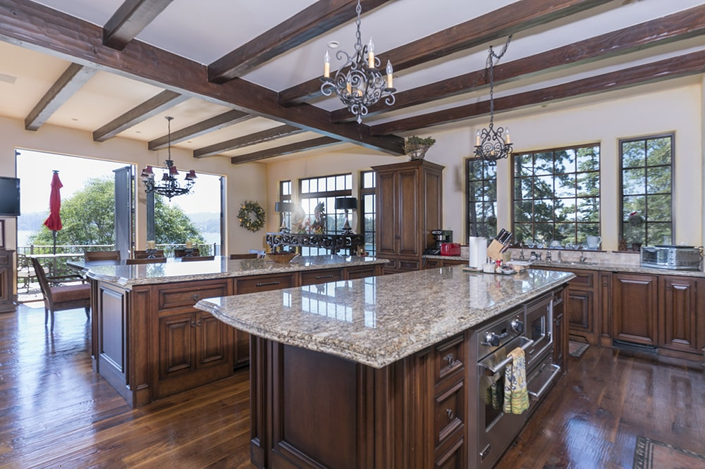 This other look at the kitchen features the exposed dark wooden beams of the ceiling along with the small chandelier that hangs over the kitchen island. Image courtesy of Toptenrealestatedeals.com.