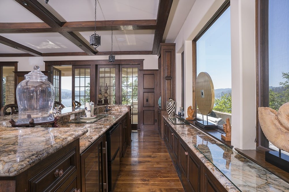 This other kitchen has a long and narrow design. It has dark brown cabinetry that matches well with the dark hardwood flooring. Image courtesy of Toptenrealestatedeals.com.