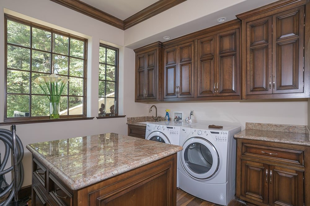 The laundry room has a couple of white washing machines that contrast the dark brown wooden cabinetry that matches the molding. Image courtesy of Toptenrealestatedeals.com.