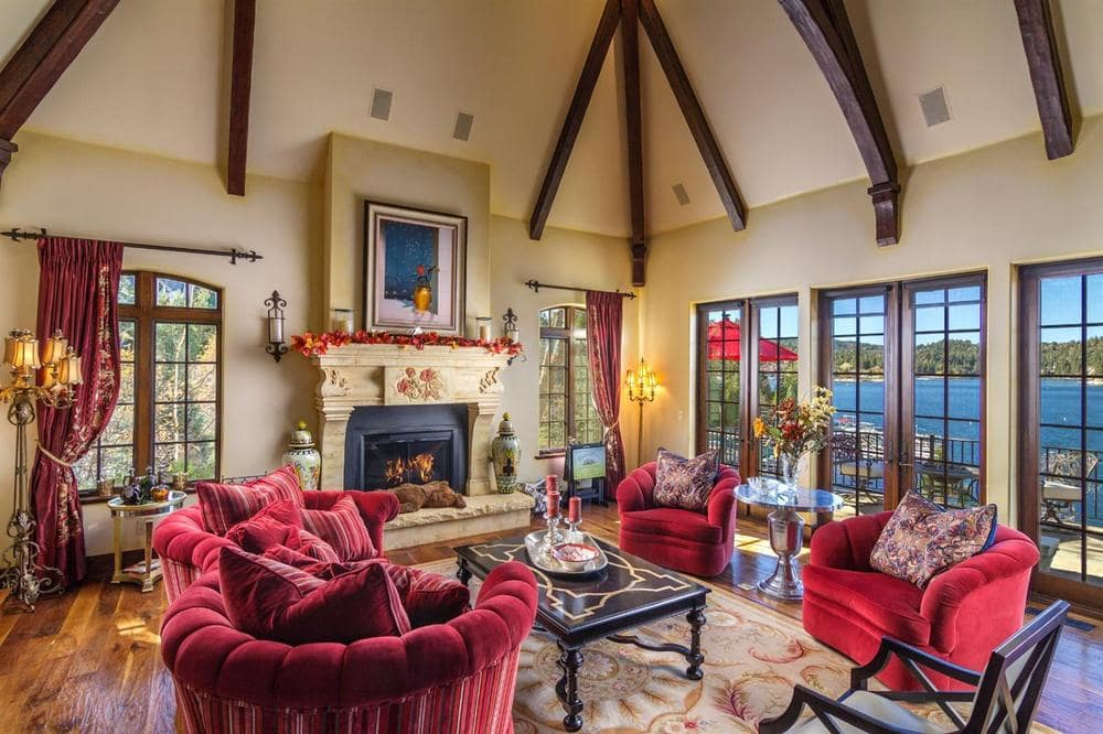 The living room has a red velevet couch that matches with the two cushioned armchairs across from the coffee table. Image courtesy of Toptenrealestatedeals.com.