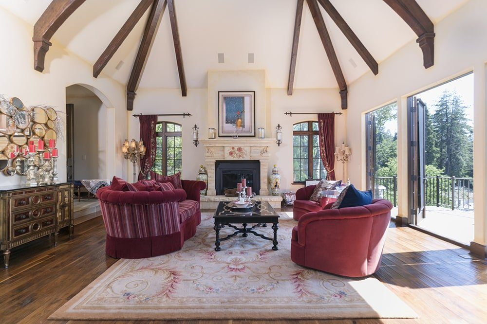 This other look at the living room showcases the fireplace with a beige mantle that blends with the wall that is flanked by tall windows. Image courtesy of Toptenrealestatedeals.com.