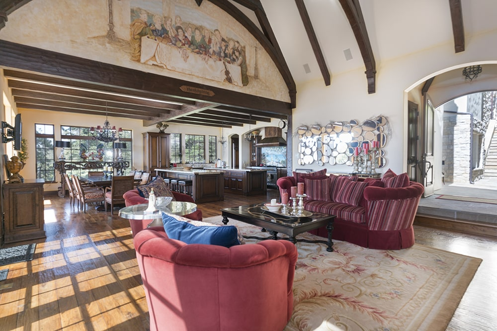 This other view of the living room shows the tall arched ceiling with exposed beams that complement the beige tone as well as the mural. Image courtesy of Toptenrealestatedeals.com.