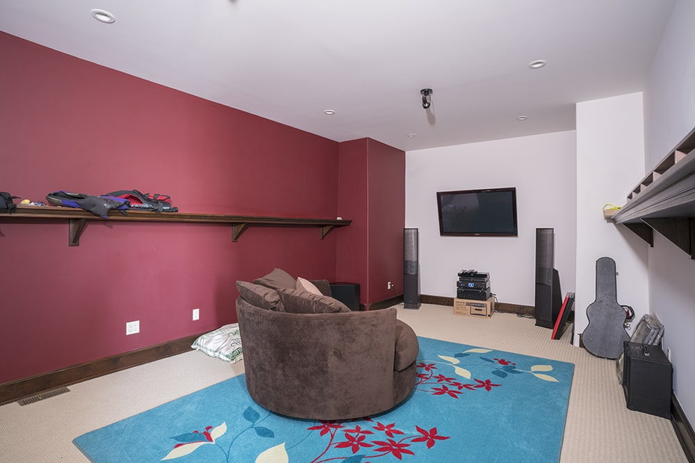 This is the music room with a brown curved sofa on a colorful area rug that contrasts the red wall. Image courtesy of Toptenrealestatedeals.com.