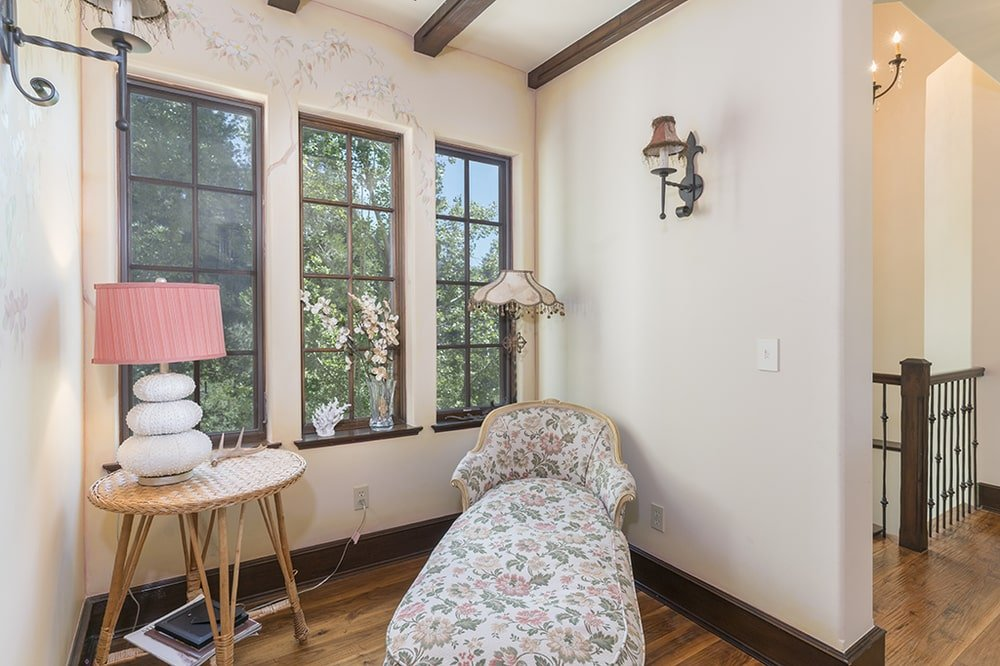 Just a few steps from the second-floor landing is this reading nook with a cushioned armchair by the windows. Image courtesy of Toptenrealestatedeals.com.