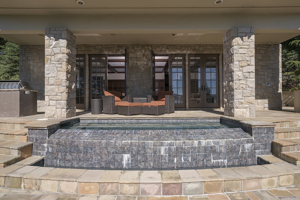 This is a look at the back covered patio fitted with a set of outdoor sofa just outside the glass doors. Image courtesy of Toptenrealestatedeals.com.