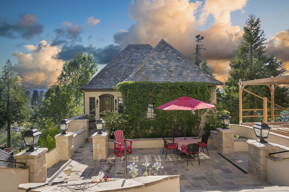 This is the outdoor patio with an outdoor dining area adorned with an umbrella and a wall of creeping plants by the back entrance. Image courtesy of Toptenrealestatedeals.com.