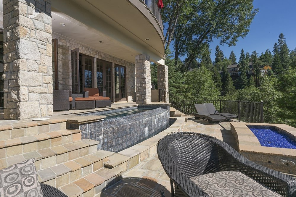 This view of the back of the house shows the pool surrounded by beige stone walkways and various sitting areas to better enjoy the landscape. Image courtesy of Toptenrealestatedeals.com.