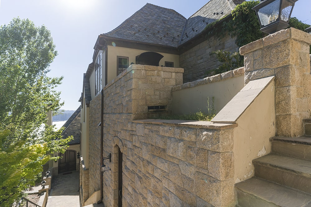 This is a look at the concrete steps and walkway that leads to the back entrance of the house. Image courtesy of Toptenrealestatedeals.com.