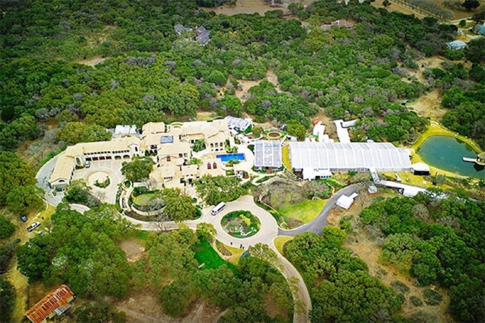 This is an aerial view of the property showcasing the vast area of the estate surrounded by lush green landscaping filled with trees. Image courtesy of Toptenrealestatedeals.com.