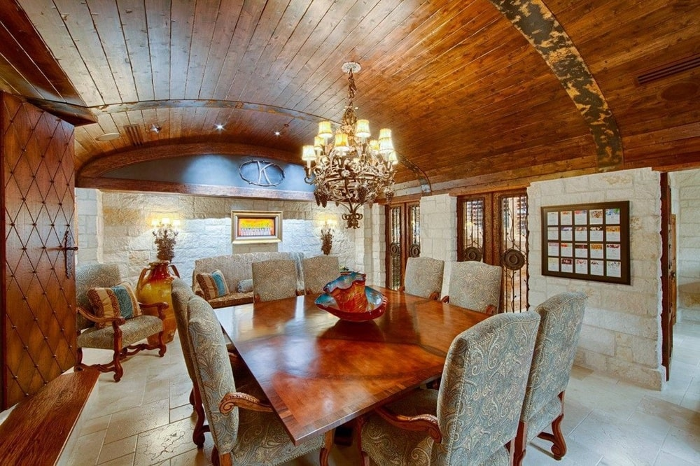 This other dining room has a wooden cove ceiling that hangs a chandelier over the rectangular wooden dining table. Image courtesy of Toptenrealestatedeals.com.
