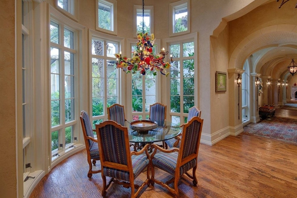 This is a breakfast nook with a small glass-top round dining table topped with a colorful chandelier beside a row of tall windows. Image courtesy of Toptenrealestatedeals.com.