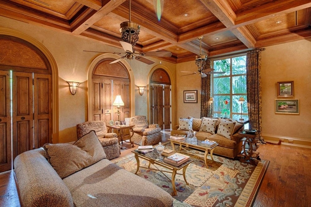 This family room has a wooden coffered ceiling with a ceiling fan over the coffee table flanked by sofas. Image courtesy of Toptenrealestatedeals.com.