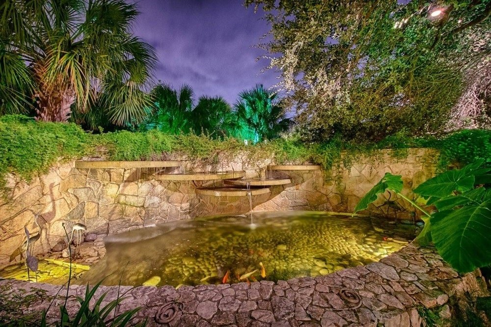 This is a close look at the fishpond adorned with tall trees, shrubs and outdoor lighting. Image courtesy of Toptenrealestatedeals.com.