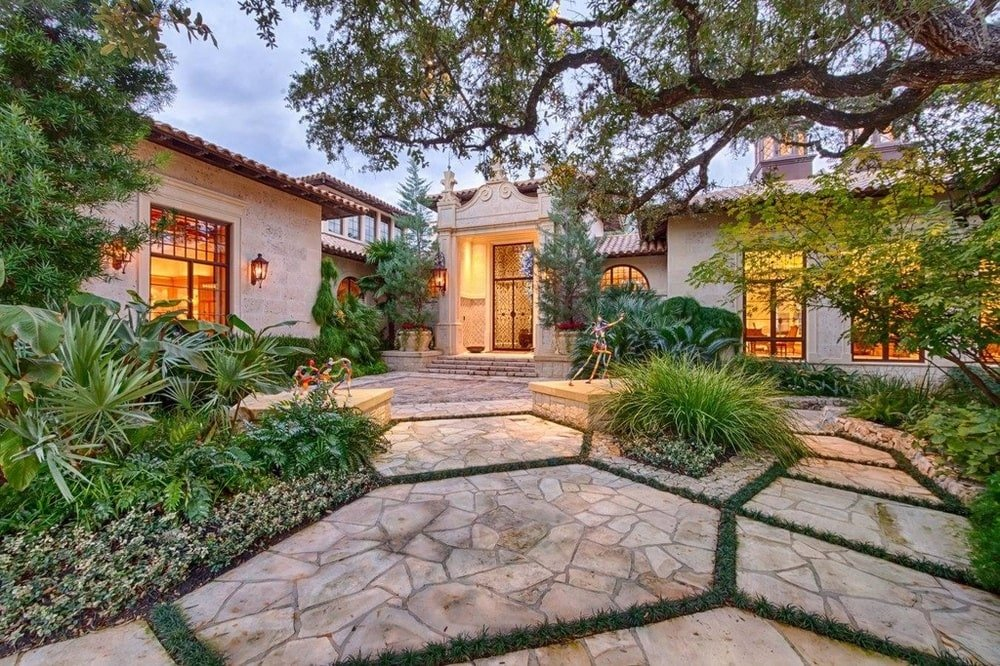 This is the front of the house with a mosaic stone walkway adorned with shrubs leading to the main entrance of the house. Image courtesy of Toptenrealestatedeals.com.
