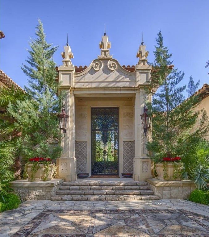This is a close look at the main entrance of the house with a, intricate concrete structure housing the wrought-iron glass main door. This is flanked by tall trees and shrubs. Image courtesy of Toptenrealestatedeals.com.
