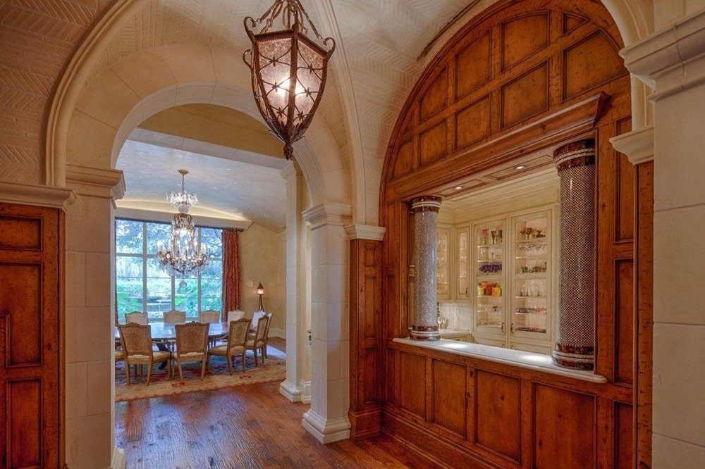 This is the hallway leading to the dining room with a pendant light in the middle and a window counter connected to the kitchen. Image courtesy of Toptenrealestatedeals.com.