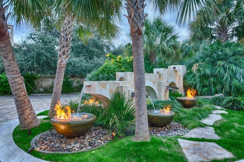 This is a close look at the decorative landscaping with fountains, shrubs and rocks beside the concrete slab walkway. Image courtesy of Toptenrealestatedeals.com.