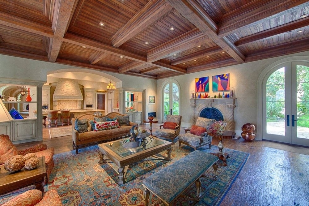The living room has a dark wooden coffered ceiling over the sofa set surrounding a glass-top coffee table across from the fireplace. Image courtesy of Toptenrealestatedeals.com.