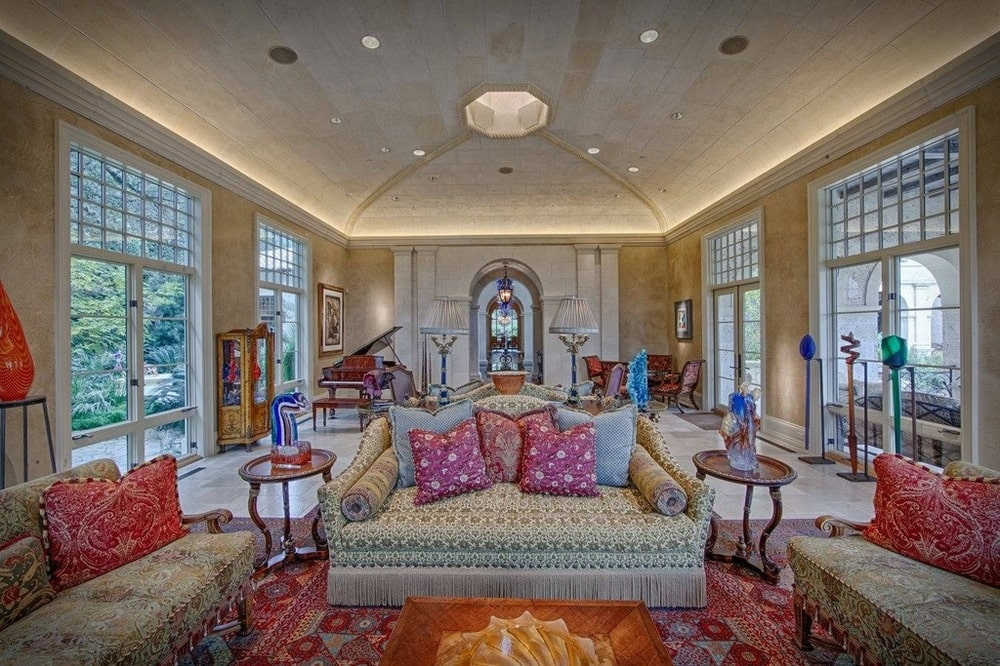 The music room has a large piano at the far corner by the tall windows. There is also a sofa topped with a cove ceiling. Image courtesy of Toptenrealestatedeals.com.