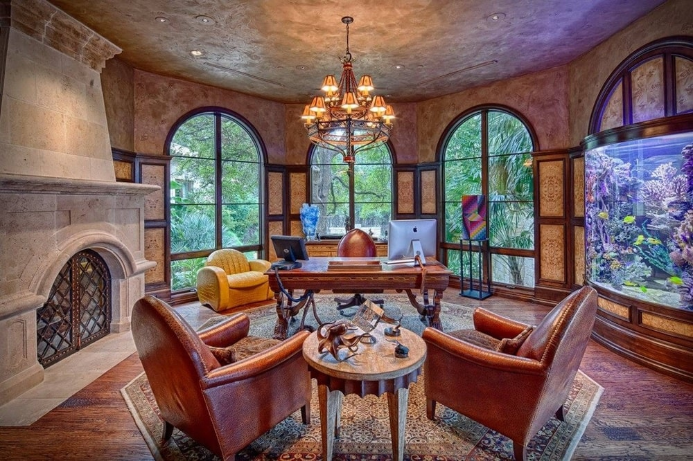 The home office has tall arched windows behind the wooden desk at the middle of the room with a fireplace on the side. Image courtesy of Toptenrealestatedeals.com.