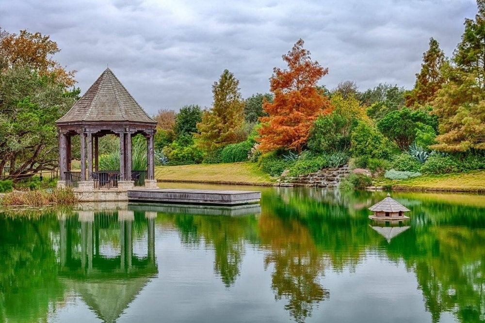 This is a view of the large pond surrounded by landscaping that has a gazebo and colorful trees in the background. Image courtesy of Toptenrealestatedeals.com.