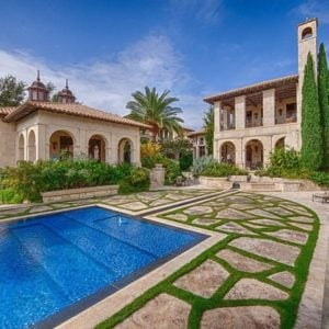 This is a look at the back of the house from the vantage of the poolside area. You can see here the beige exteriors of the house adorned with multiple arches and the green landscape of tall trees and shrubs. Image courtesy of Toptenrealestatedeals.com.