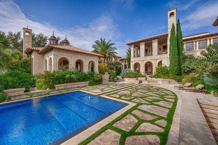 This is a look at the back of the house from the vantage of the poolside area. You can see here the beige exteriors of the house adorned with multiple arches and the green landscape of tall trees and shrubs.