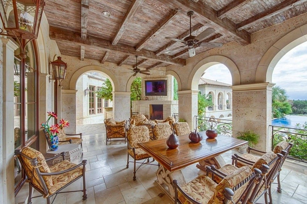 This is the spacious covered terrace bordered with arches that bring in an abundance of natural lighting to the wooden beamed ceiling, outdoor dining area and sitting areas. Image courtesy of Toptenrealestatedeals.com.